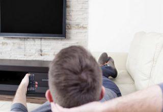 Die 7 lustigsten Berufe der Welt / auf dem Foto: Ein Mann - vielleicht ein professioneller Fernsehzuschauer - liegt auf dem Sofa und schaltet auf den nächsten Fernsehkanal.