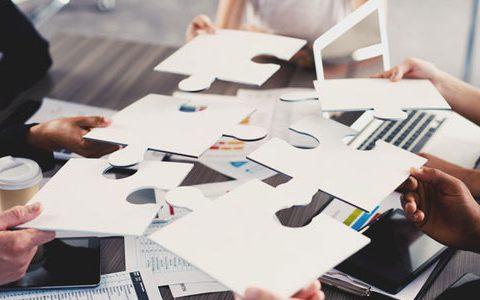 Firma ohne Chef - Funktioniert das?/ auf dem Foto: Die Team-Mitglieder arbeiten gleichberechtigt zusammen und setzen Puzzleteile zusammen.
