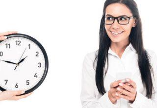 Brückenteilzeitgesetz - fröhliche Frau schaut auf eine große Uhr, die von jemanden ins Bild gehalten wird. Weißer Hintergrund. Die Frau ist weiß gekleidet und hat schwarze Haare. Die Uhr hat ein wießes Zifferblatt schwarze Zeiger und einen schwarzen Rand.