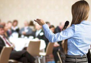 Checkliste für das perfekte Tagungshotel / auf dem Foto: Geschäftsfrau hält einen Vortrag auf einer Konferenz mit vielen Teilnehmern.