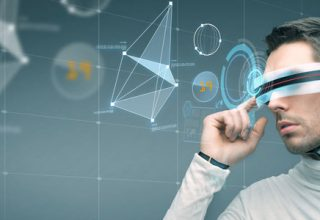 Berufe der Zukunft - die Top 6 / auf dem Foto: Ein Mann mit futuristischer 3D-Brille und Mikrochip-Implantat arbeitet an einem virtuellen Bildschirm.