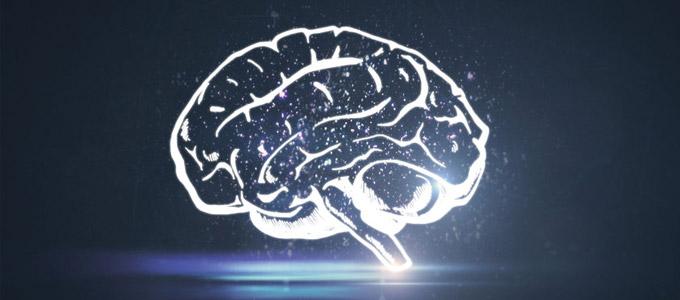 Auffassungsgabe trainieren / auf dem Foto: Skizze eines leuchtenden Gehirns auf dunklem Hintergrund.