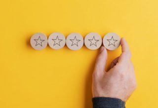 Online Reputationsmanagement für Unternehmen und Arbeitnehmer / auf dem Foto: Eine Hand fügt vier runden Holzstücken mit Sternchen, die auf einem gelben Untergrund liegen, ein fünftes hinzu.