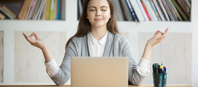 Stressprävention - Achtsamkeit im Job / auf dem Foto: Eine Büroangestellte sitzt vor dem Computer und meditiert.