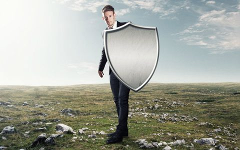 Mann mit einem Schutzschild aus Metall steht im Feld