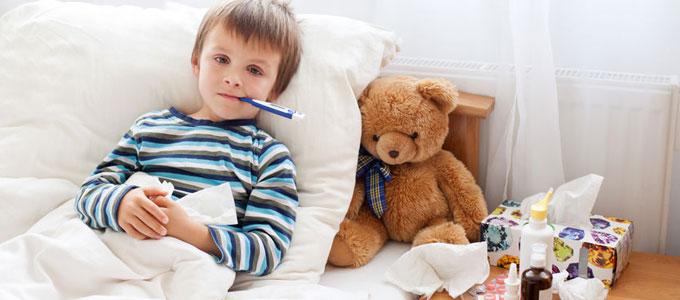 Kind krank: Sonderurlaub, Krankschreibung und Kinderkrankengeld / auf dem Foto: Ein Junge liegt krank im Bett und hat ein Fieberthermometer im Mund. Auf dem Nachttisch stehen Medikamente und Taschentücher.