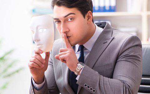 Ein Mann hält eine Maske in seiner Hand und den erhobenen Zeigefinger vor seinem Gesicht