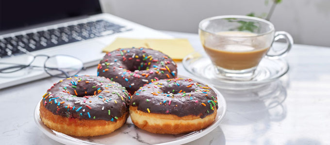 Drei leckere Donuts mit Schoko-Glasur neben einem Laptop