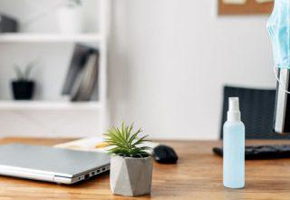 Schreibtisch mit Mundschutz und einer Sprayflasche