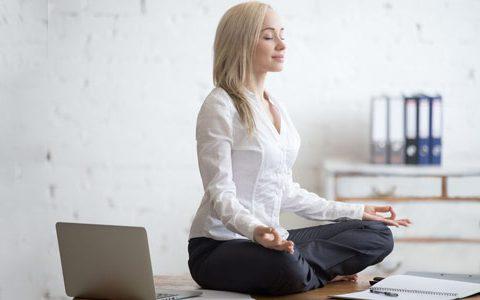 eine Frau sitzt im Lotussitz und meditiert