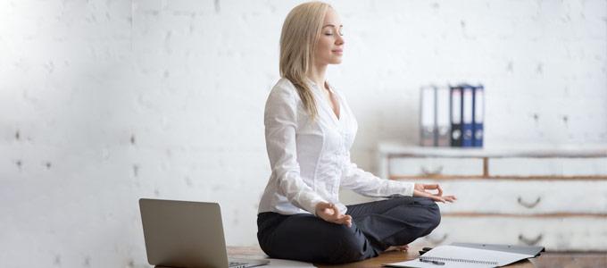Eine Frau sitzt im Lotussitz und meditiert im Büro
