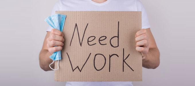 Ein Schild auf dem Need Work steht und und eine Maske in der rechten Hand der Person die das Schild hält