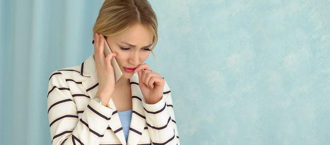 Eine Frau hält einen Hörer in der hand mit einem traurigen Gesicht
