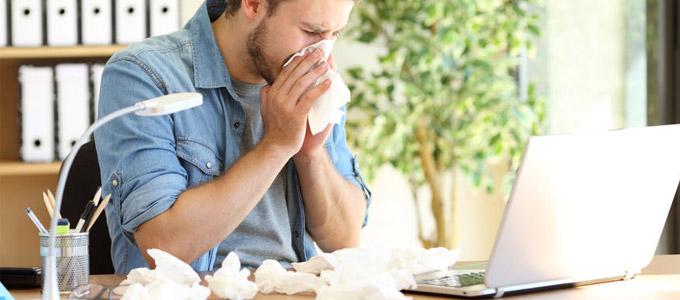 Ein Mann sitzt vor dem Laptop und putzt sich die Nase mit einem Taschentuch