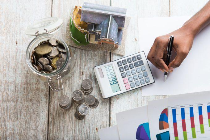 Es geht um eine Finazierung, man sieht eine Hand, einen Taschenrechner und Münzen