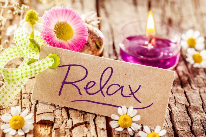 Ein Bild mit dem Schriftzug Relax und einer Kerze und einer Blume