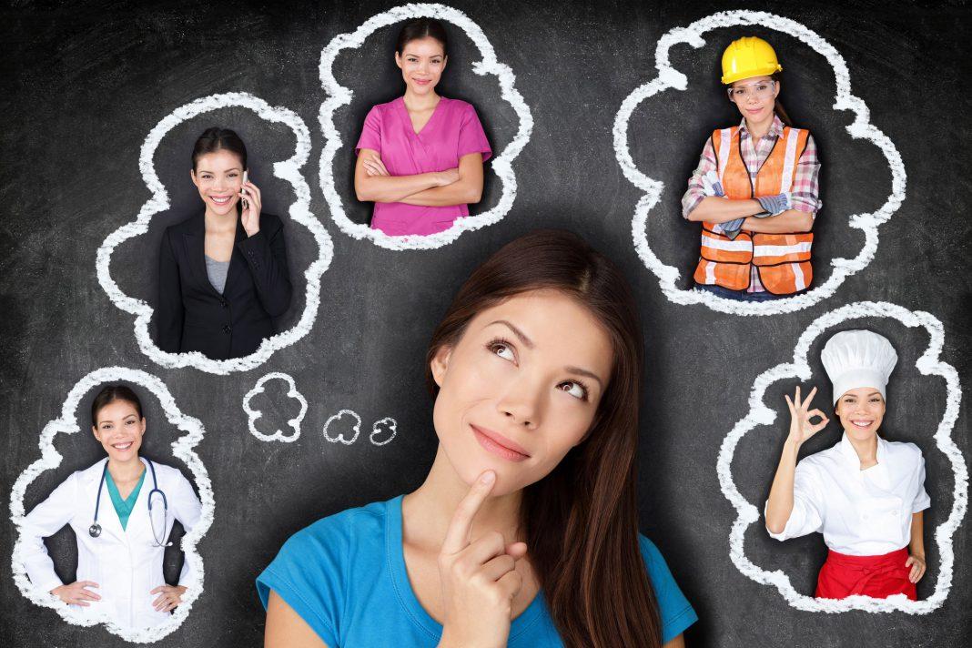 Student Denken der Zukunft. Junge asiatische Frau erwägt Karrieremöglichkeiten lächelnd nach oben auf Sprechblasen auf einer Tafel mit verschiedenen Berufen