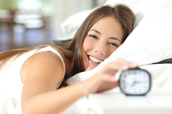 Glückliche Frau aufwachen und den Wecker ein guter Tag Abschalten mit