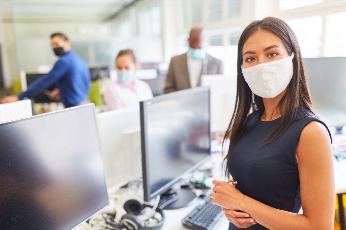 Man sieht eine Frau mit Maske in einem Büro