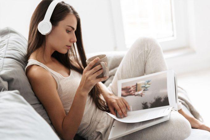 Ein Frau entspannt mit Kopfhören und einer Tasse Tee, während sie in einem Buch blättert