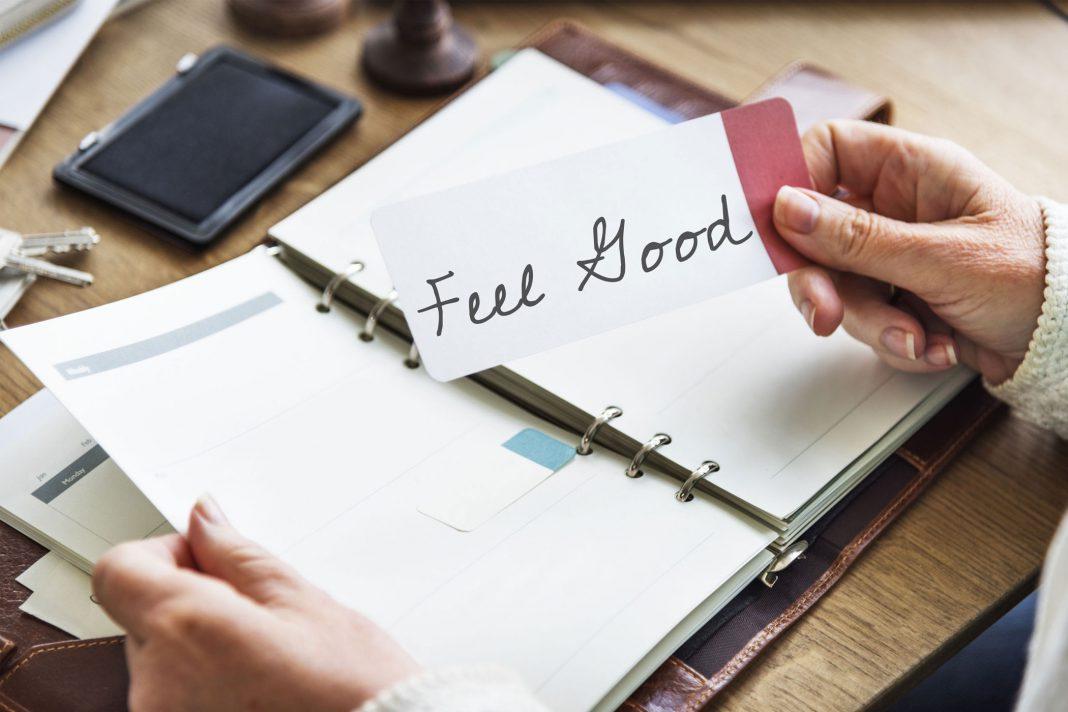 Man sieht einen Terminplaner davor eine Hand, die einen Zettel mit der Aufschrift Feel Good hält