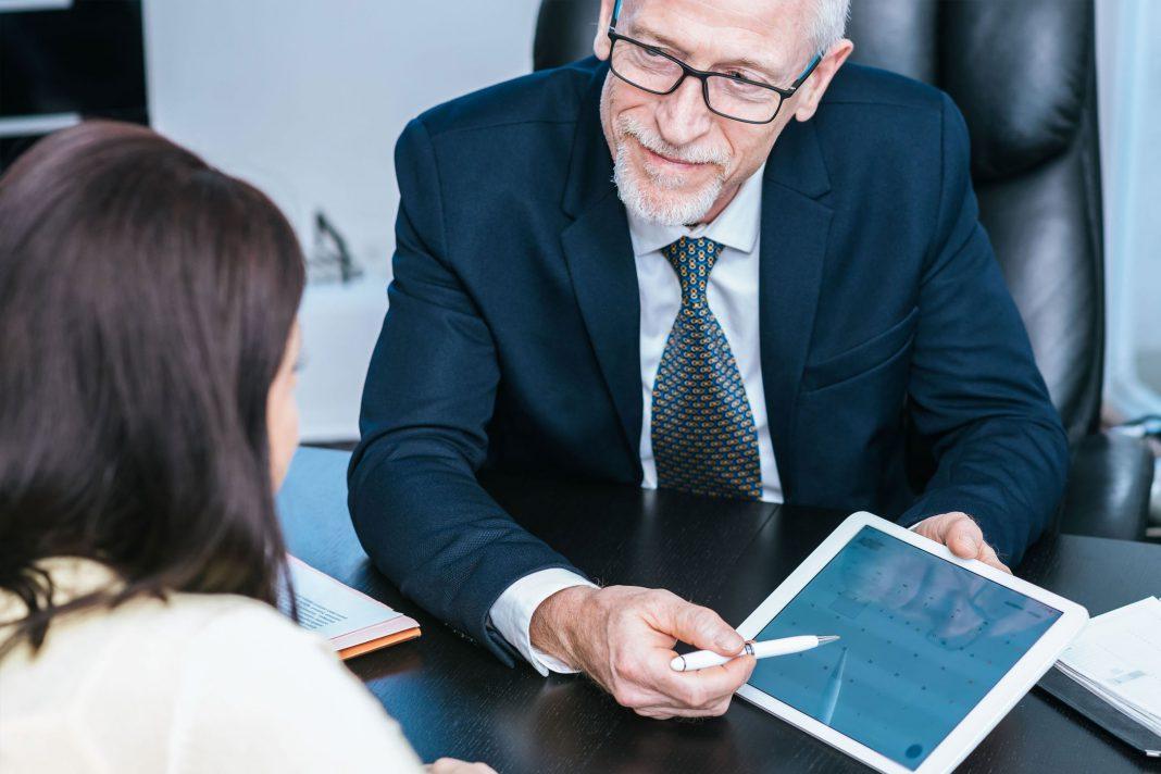 Eine älterer Mann zeigt einer Frau etwas auf dem Tablet
