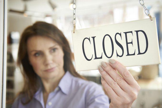 """Eine Frau hält ein Zeichen mit dem Wort """"Closed"""""""
