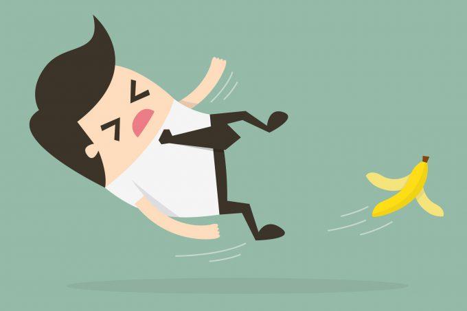 Ein Cartoon*Männchen rutscht auf einer Banane aus
