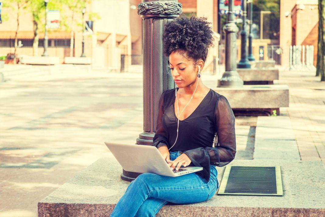 Eine Frau arbeitet draußen mit einem Laptop