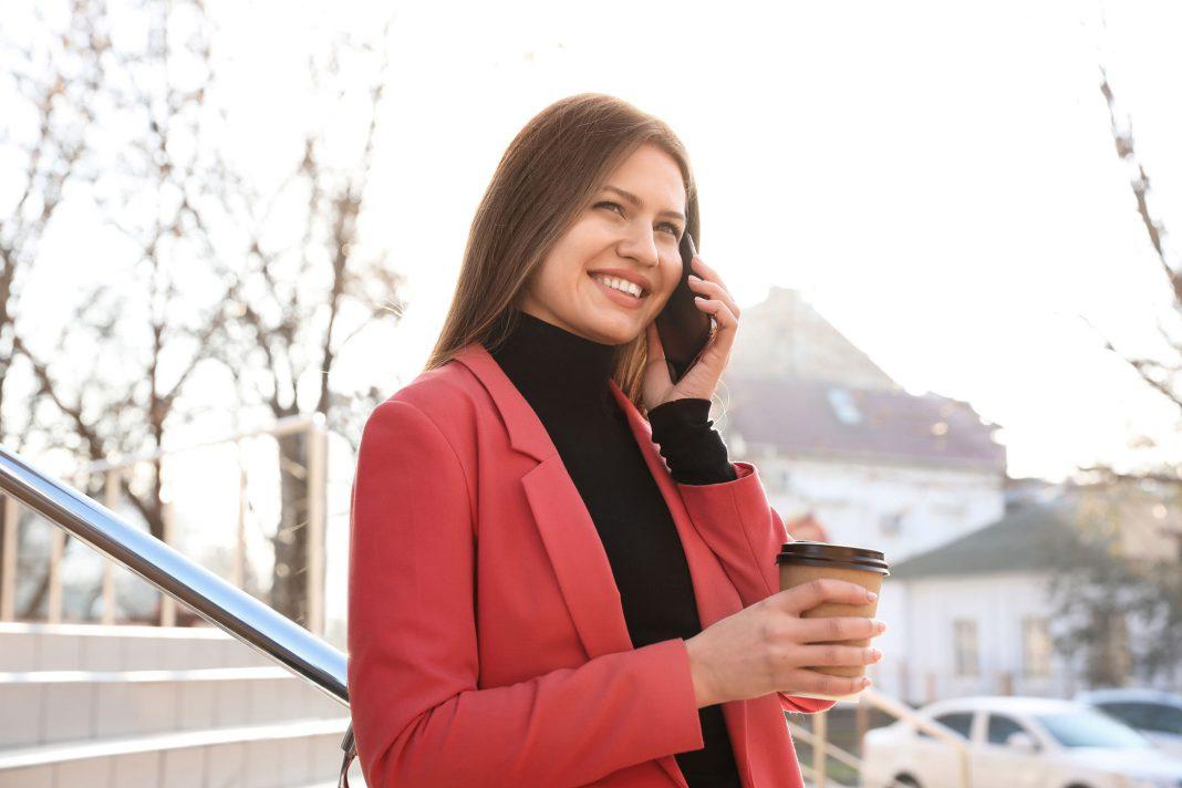 Ein Frau führt ein Handygespräch im WInter mit einem Kafee in der Hand