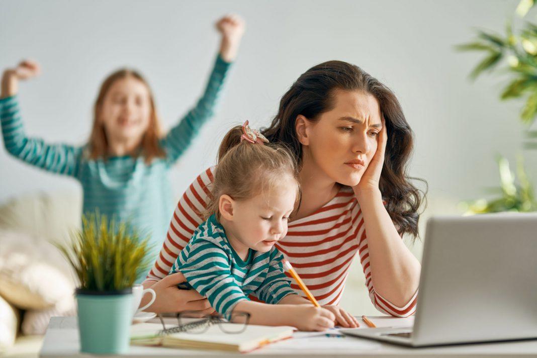 Eine Frau versucht Arbeit und Kinder im Home Office unter einem Hut zu bringen