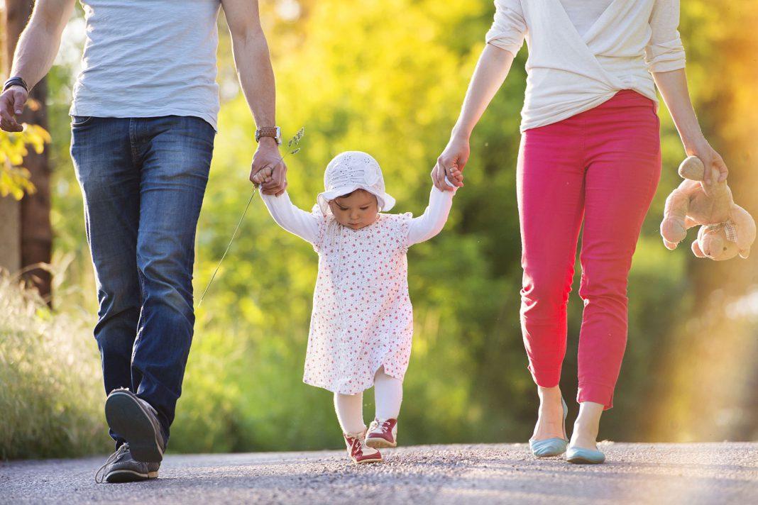Ein Paar hält draußen ein Kleinkind an den Händen, während es versucht zu gehen.