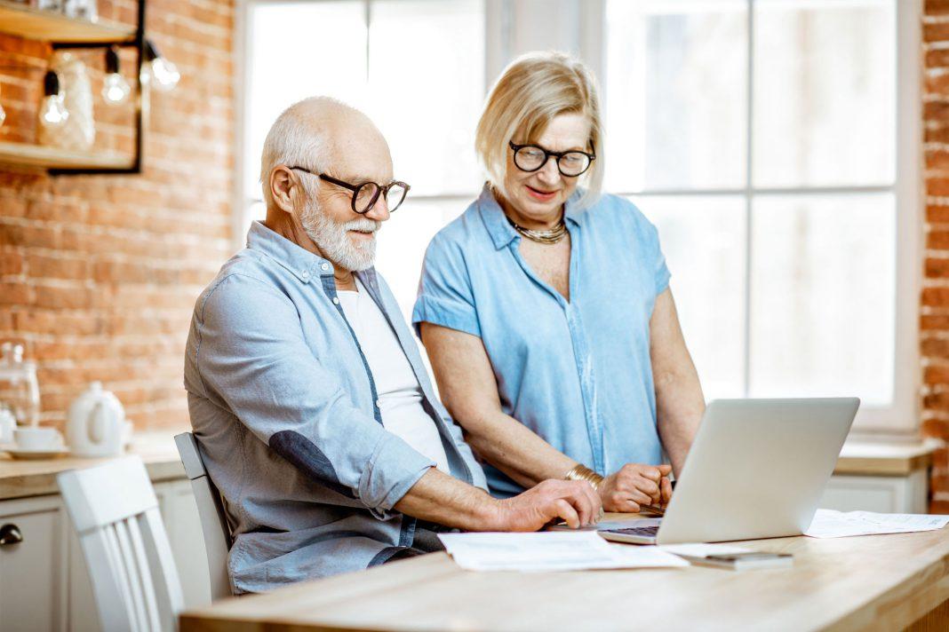 Ein älteres Paar sitzt vor einem Notebook.