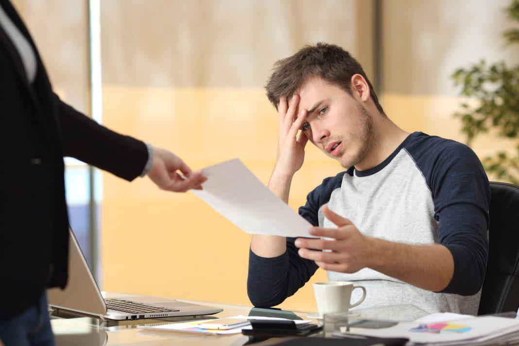 Eine Person bekommt eine negative Nachricht per Zettel überreicht.