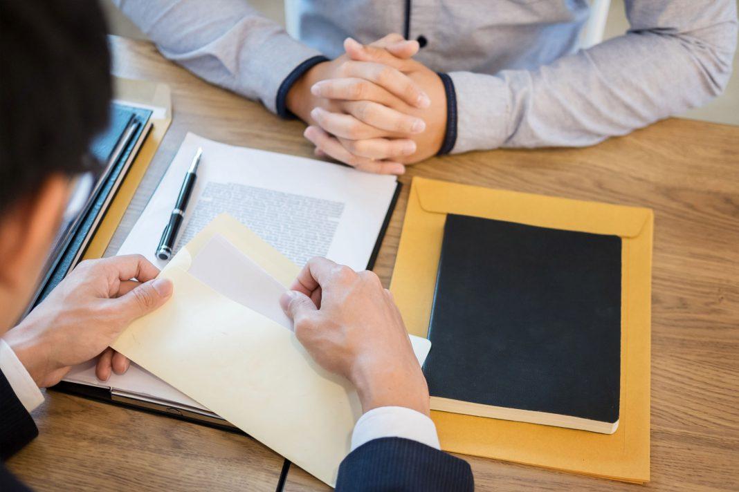 Eine Person öffnet einen Brief, der eine Kündigung enthält, während eine andere Person daneben sitzt.