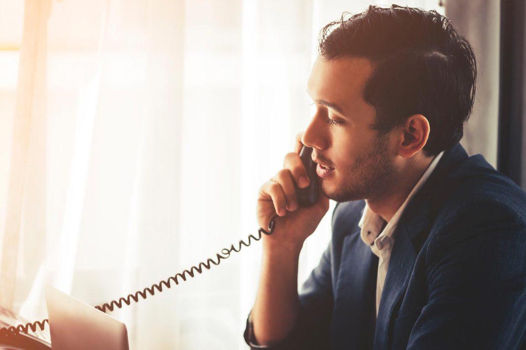 Ein Arbeiter sagt einen Termin per Telefon ab