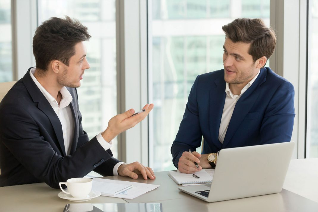 Zwei männliche Büroarbeiter beim Gespräch