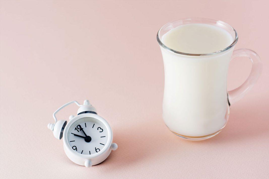 Ein Glas mit warmer Milch hilft beim Einschlafen, hier dargestellt neben einer kleinen Uhr