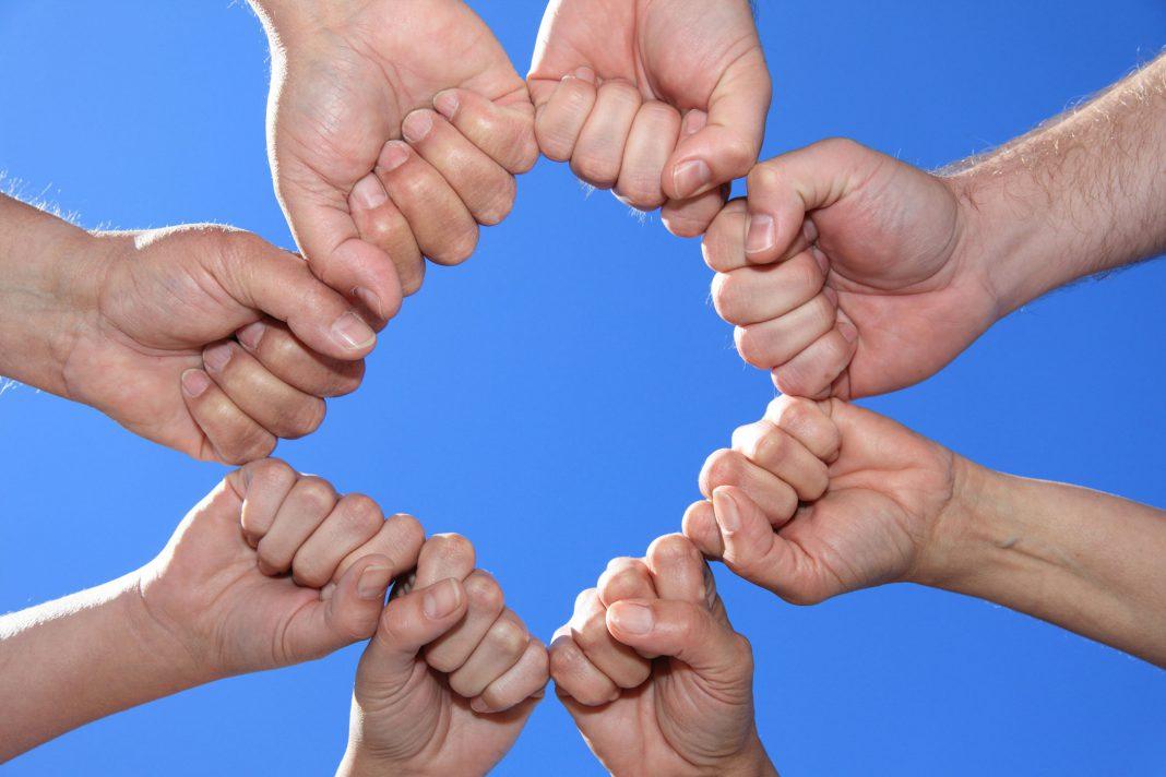 acht geballte Hände bilden zusammen einen Kreis