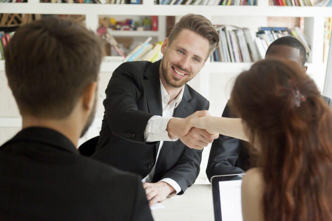 Zwei Personen besiegeln den neuen Arbeitsvertrag mit einem Handschlag
