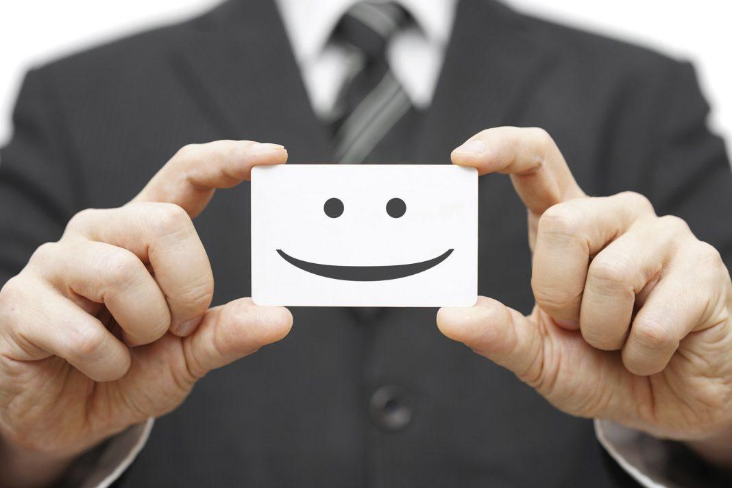 Eine Person hält eine Visitenkarte mit einem Smiley drauf