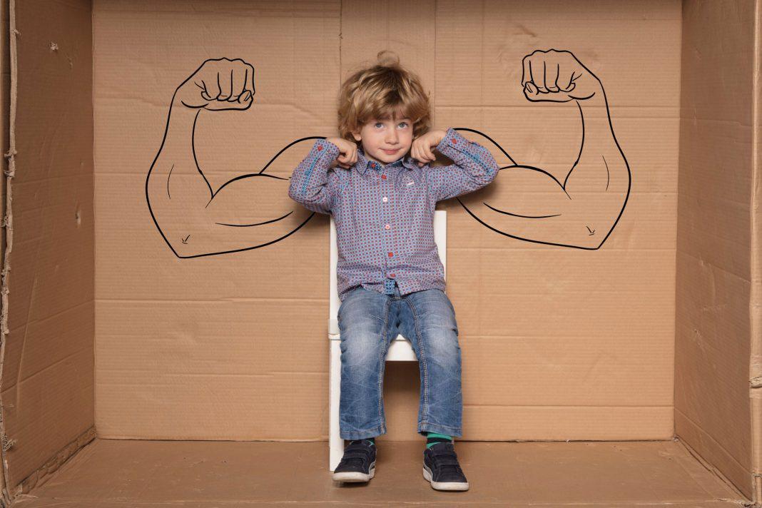 Ein Kind mit gezeichneten starken Armen im Hintergrund